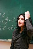 Young woman thinking near the blackboard royalty free stock image