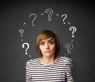 Young woman thinking with question mark circulation around her h Royalty Free Stock Image