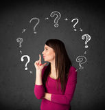 Young woman thinking with question mark circulation around her h Royalty Free Stock Images
