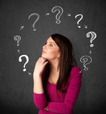Young woman thinking with question mark circulation around her h Royalty Free Stock Photography