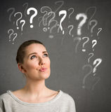 Young woman thinking with question marks over head. Young woman makes a face and thinking with question marks over head royalty free stock image