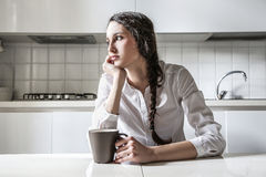 Young woman thinking sitting in the kitchen Stock Image