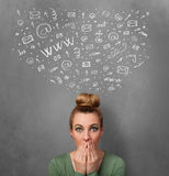 Young woman thinking with social network icons above her head Stock Photo