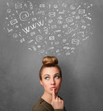 Young woman thinking with social network icons above her head Royalty Free Stock Images
