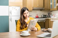 Woman Analyzing Newspaper Game Carefully. Young woman thinking while solving crossword puzzle at table during breakfast time stock photography