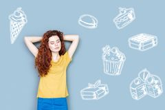 Young woman thinking about sweets while being on a diet. Favorite sweets. Calm dreamy woman closing her eyes and thinking about delicious sweets while being on a royalty free stock image