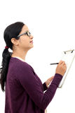 Young woman thinking while taking notes Royalty Free Stock Photo