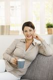 Young woman thinking with tea in hand Stock Photos