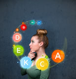 Young woman thinking with vitamins circulation around her head Royalty Free Stock Photography