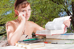 A young woman thinking whilst studying Royalty Free Stock Photography