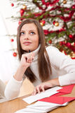 Young woman thinking while writing Christmas card Royalty Free Stock Images
