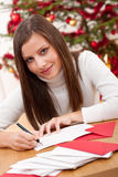 Young woman thinking while writing Christmas card Royalty Free Stock Photo