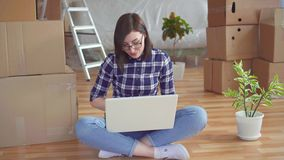 The young woman thought on the background of repairs or boxes to move. Portrait young woman thought on the background of repairs or boxes to move stock video footage