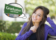 Young Woman with Thought Bubble of Graduation Green Road Sign Stock Image