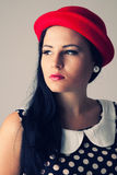 Young woman with thoughtful look in red hat Stock Photos