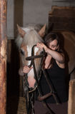Young woman threading  halter on her horse in stable. Young woman threading halter on her horse in stable Royalty Free Stock Images