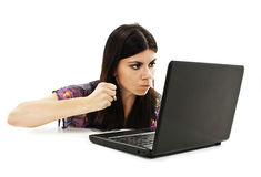 The young woman threatens with a fist to the virtual interlocutor Royalty Free Stock Photos