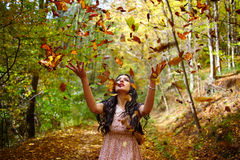 Young woman throwing autumn leaves in the air Royalty Free Stock Photos