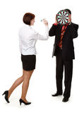 Young woman throwing darts. At a target held by the man, isolated on a white background Stock Photography