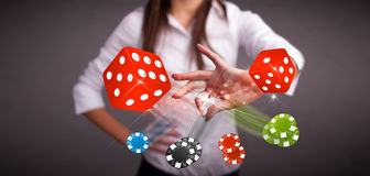Young woman throwing dices and chips Stock Photos