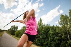 Young woman throwing a javelin in nature Stock Photo