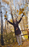 Young woman throwing leaves in the air Royalty Free Stock Photography
