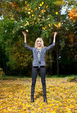 Young woman throwing leaves in the air. Young woman throwing leaves in an autumn park stock image