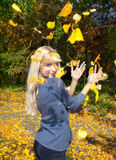 Young woman throwing leaves in the air. Young woman throwing leaves in an autumn park stock photography
