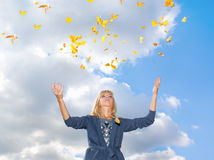 Young woman throwing leaves in the air Royalty Free Stock Images