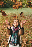 Young woman throwing leaves in the air Stock Photo