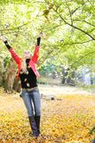 Young woman throwing leaves in park Royalty Free Stock Photo