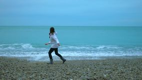 Young woman throwing pebbles into ocean, foamy waves splashing ashore in slow-mo. Stock footage stock video footage