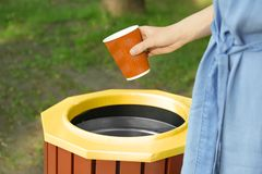 Young woman throwing plastic cup in litter bin outdoors. Closeup Royalty Free Stock Photo