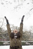 Young woman throwing snow into air in park Royalty Free Stock Photo