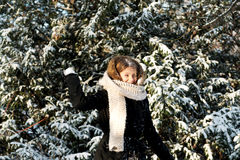 Young woman throwing snowball Stock Images