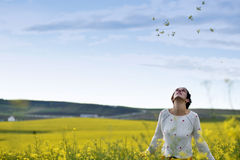 Young woman throwing yellow petals in the air Stock Photography