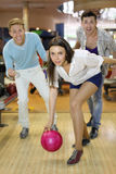Young woman throws ball in bowling Stock Photo