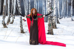 A young woman throws a card. A young woman in a red gown throwing tarot cards on the snow Royalty Free Stock Photography