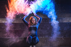 Young woman throws and dance with color powder on dark background. Beautiful young woman throws and dance with color powder on dark background Royalty Free Stock Images