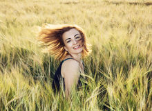 Young woman throws her hair in wheat field by sunset Stock Photography