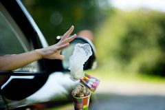 A young woman throws waste from the car - a coffee cup and a bag. Environmental pollution, selective focus, backlight