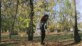 Young woman throws yellow leaves in autumn park. Beautiful girl in the coat playing with the maple leaves in the forest stock footage