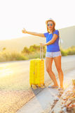 Young woman with a thumb up and yellow suitcase is traveling on Royalty Free Stock Image