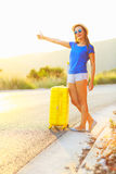 Young woman with a thumb up and yellow suitcase is traveling on Stock Photos