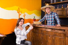 Young woman with thumbs up sitting at the bar counter next to th. Young women with thumbs up sitting at the bar counter next to the bartender wearing sombrero royalty free stock images