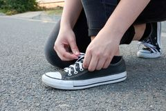 Young woman ties laces in sneakers on asphalt road in city in sp royalty free stock photography
