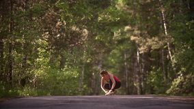Young woman ties up her sneakers and prepares for a jog. A girl with a smart watch is doing sports in the summer forest stock footage