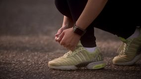 Young woman ties up her sneakers and prepares for a jog. A girl with a smart watch is doing sports in the summer forest stock video