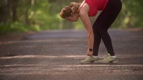 Young woman ties up her sneakers and prepares for a jog. A girl with a smart watch is doing sports in the summer forest stock video footage