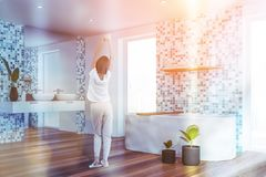 Young woman in tiled bathroom corner. Rear view of woman in pajamas standing in comfortable bathroom with tiled walls, double sink and white bathtub. Toned image royalty free stock photo
